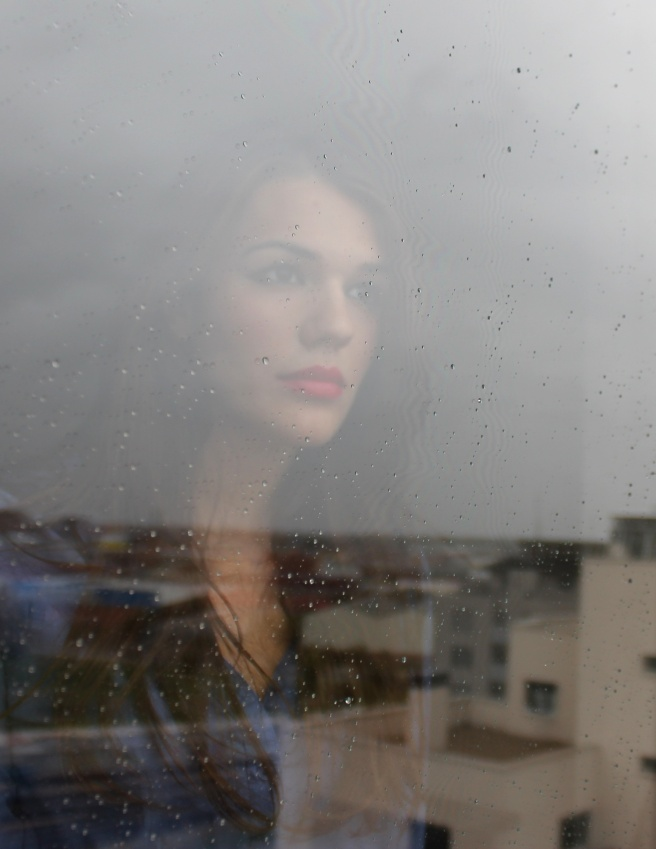 Woman standing infront of wet window